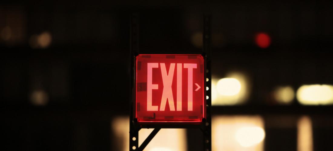 Un segnale rosso con scritto exit che punta a destra