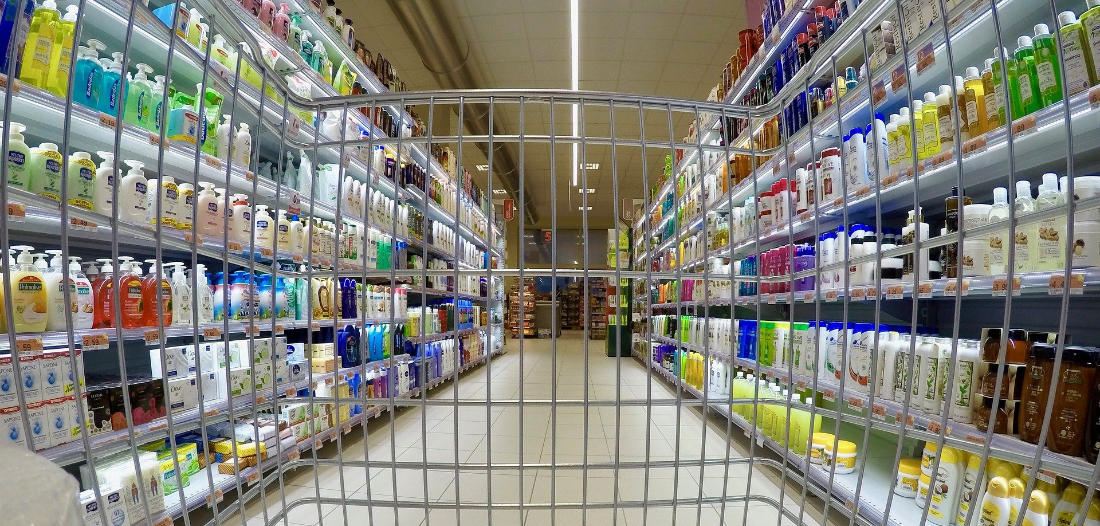 Visuale di un supermercato da dietro il carrello della spesa