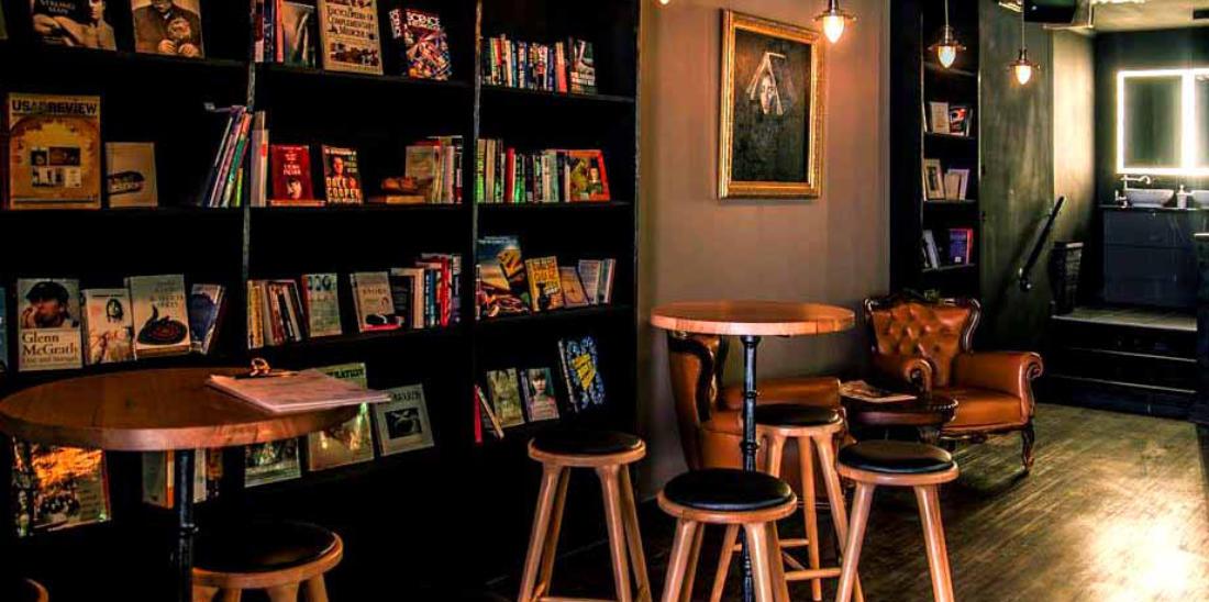 Sedie e tavolini con accanto degli scaffali con libri