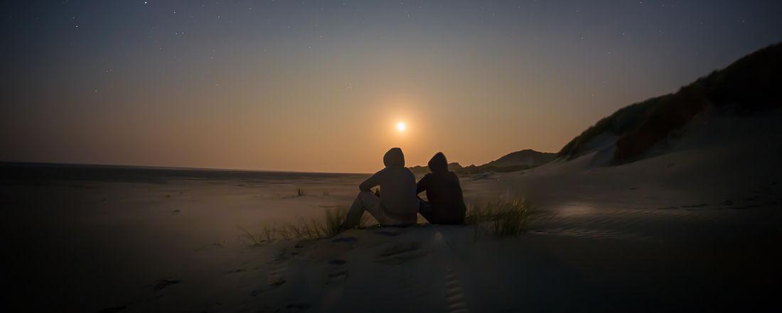 Due persone sedute al tramonto