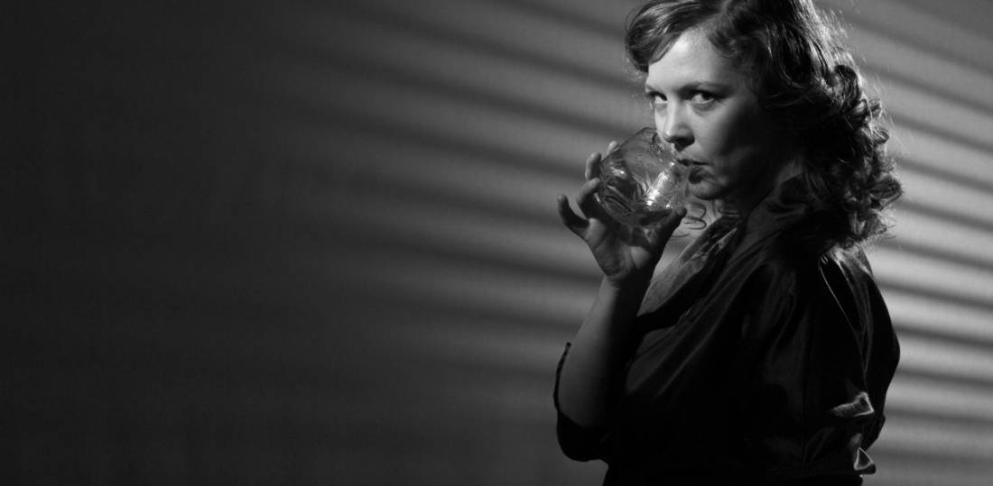 Una donna in bianco e nero che sorseggia da un bicchiere